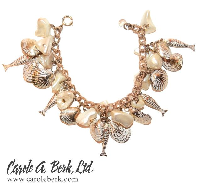 Accessocraft N.Y.C 70s seaside charm bracelet. The shells and fish and  are crafted of gold tone metal with white enamel accents. They are interspersed with pearlized  rocks making for a very unusual grouping . This is an interesting mix of elements.$145.