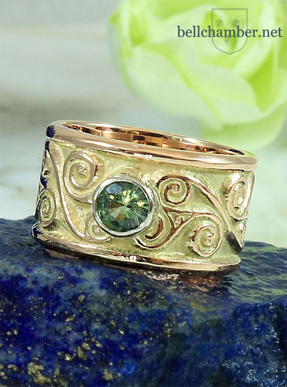 Amphreville Celtic Triskele Ring in 14 gold with 1/2 carat Green Sapphire.  Ring is 10mm wide