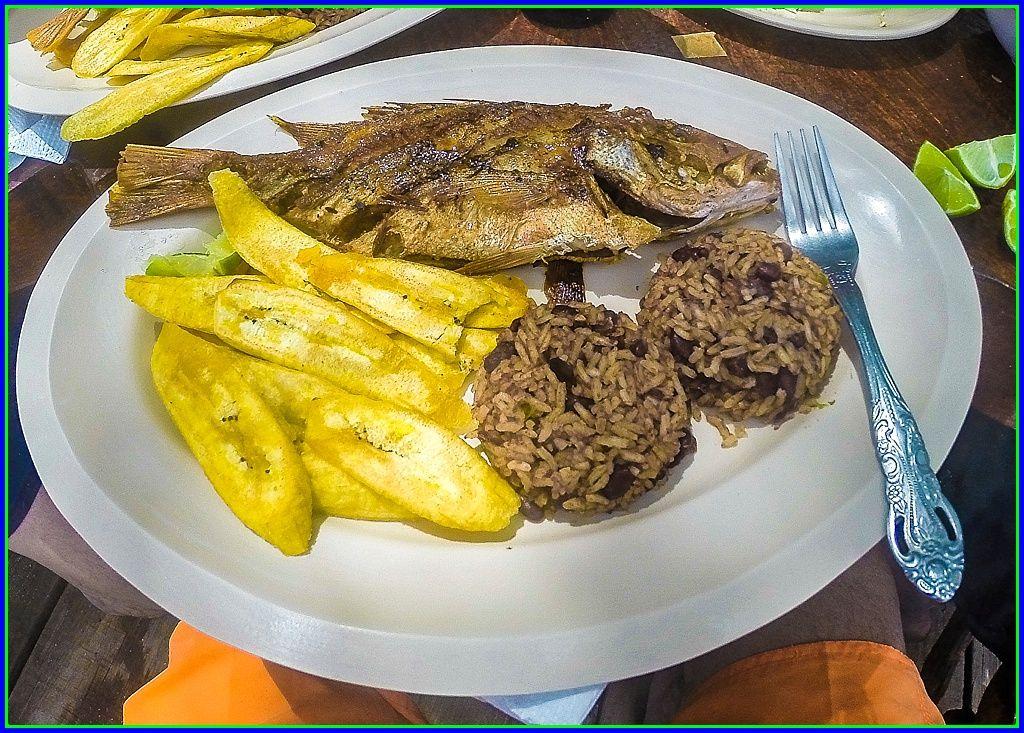 Pescado frito con arroz y frijoles, tajadas de platano...