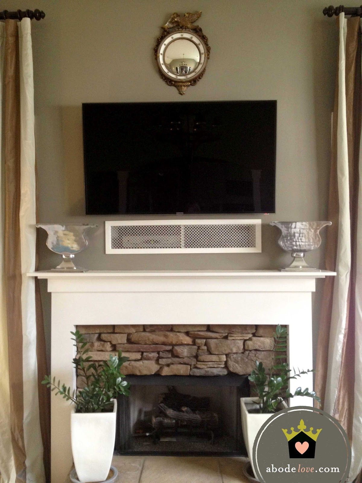play systems behind a grill above the mantel and below the tv