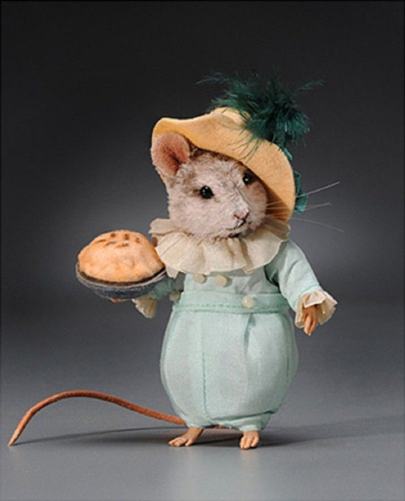 Inspired by the original Kate Greenaway illustration, Little Jack Horner is outfitted in a period costume consisting of a 2-piece aqua silk suit with ivory silk ruffles at the neck and cuffs. A jaunty felt hat trimmed in silk with a fine feather plume crowns his head. He comes complete with his Christmas pie - a custom-made pewter pie plate topped by a realistic felt crust