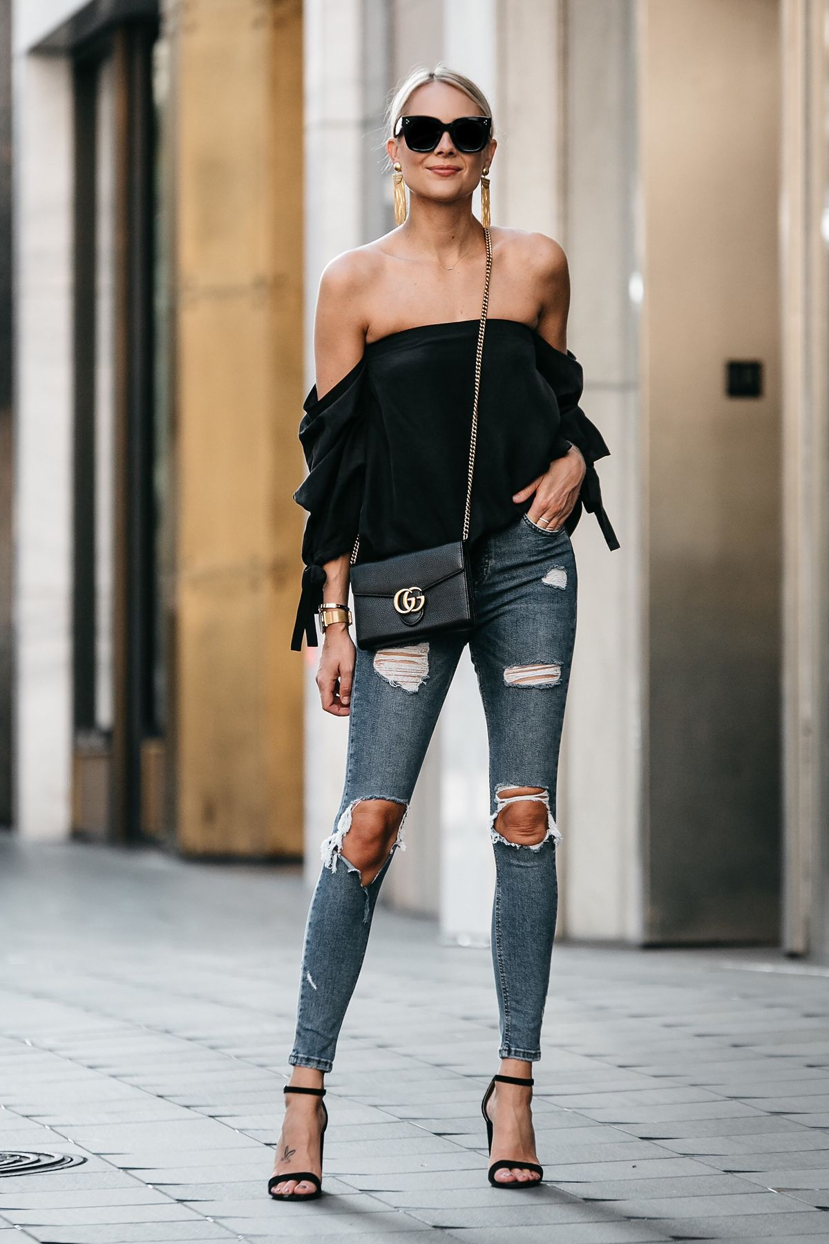 cc8ca8e813195 Blonde Woman Wearing Club Monaco Black Off-the-Shoulder Top Denim Ripped  Skinny Jeans Outfit Gucci Marmont Handbag Black Ankle Strap Heeled Sandals