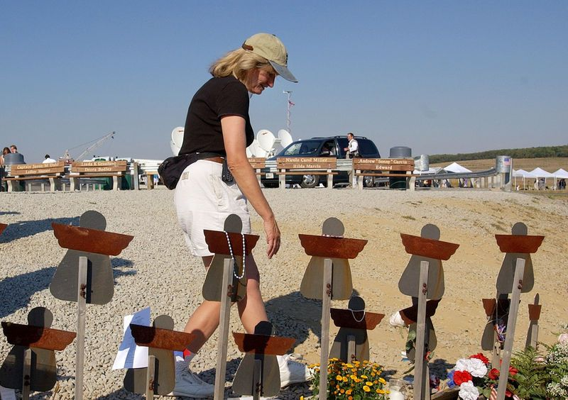 """Photo honoring United Airlines Flight 93 on Tributes.com. """"Alice Hoglan, mother of Flight 93 victim Mark Bingham, looks for the marker with her son's name on it at the temporary memorial to Flight 93 near Shanksville, Pa., Tuesday, Sept. 10, 2002. President Bush will lay a wreath at the crash site Wednesday, Sept. 11 to mark the anniversary of the terrorist"""""""