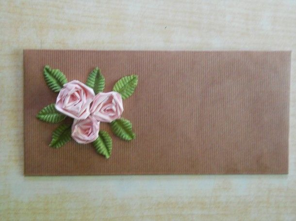 An envelope decorated with paper quilling roses The envelope