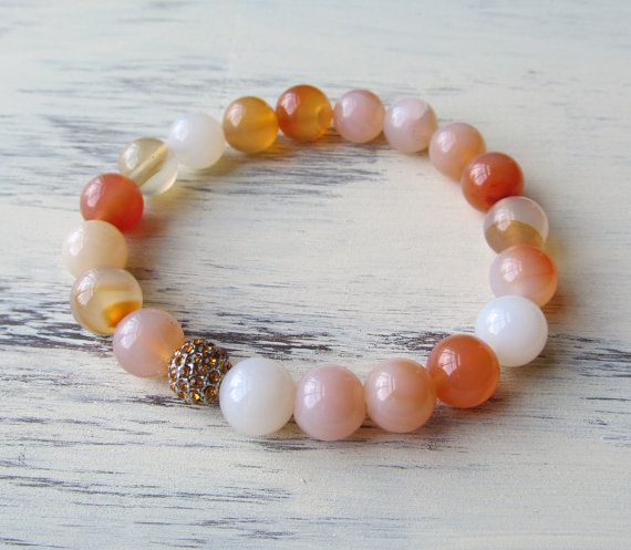 This beautiful bracelet is composed of 10 mm (large) natural agate beads accented with a golden amber pave crystal bead.    Agate is a wonderful stone for healing and protection ~ considered power stones that provide stability and grounding. It is also known as a stone to encourage strength and courage. Natural Agate is said to foster love and soothe emotions. Associated primarily with the heart chakra..