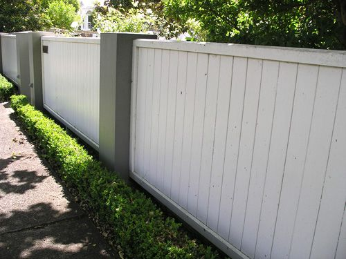 White wooden fence with masonry looking pillars.