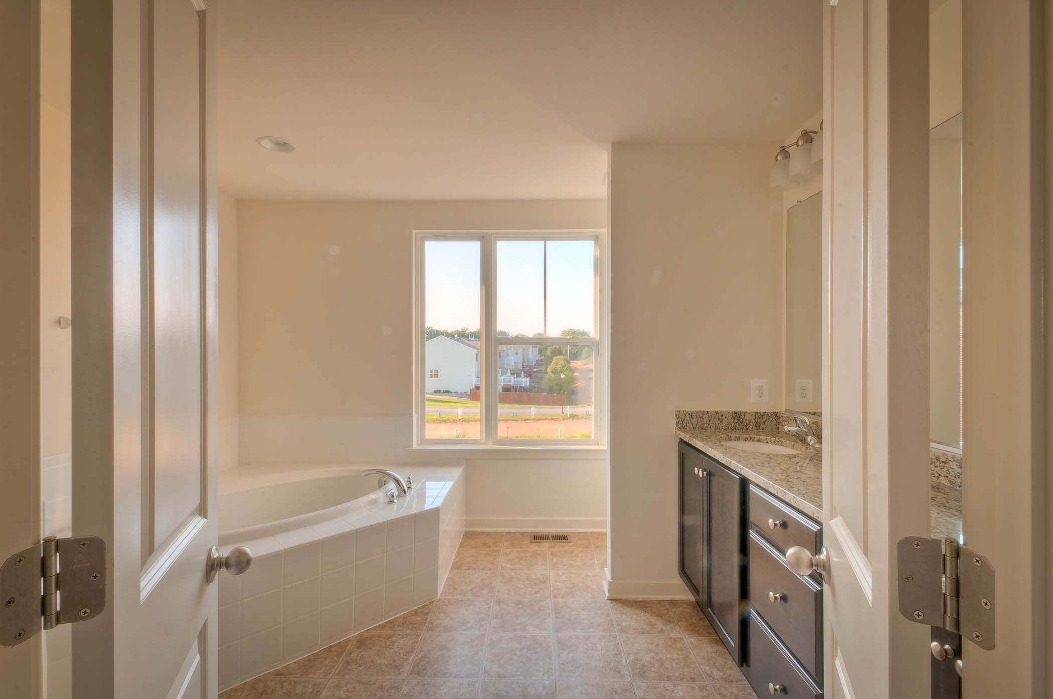 Townhome in Frederick, MD. Double doors lead you into your owner's bath. Dark cabinets, light granite, and a separate tub and shower leave this bathroom spacious. Click on the picture for the floor plans.