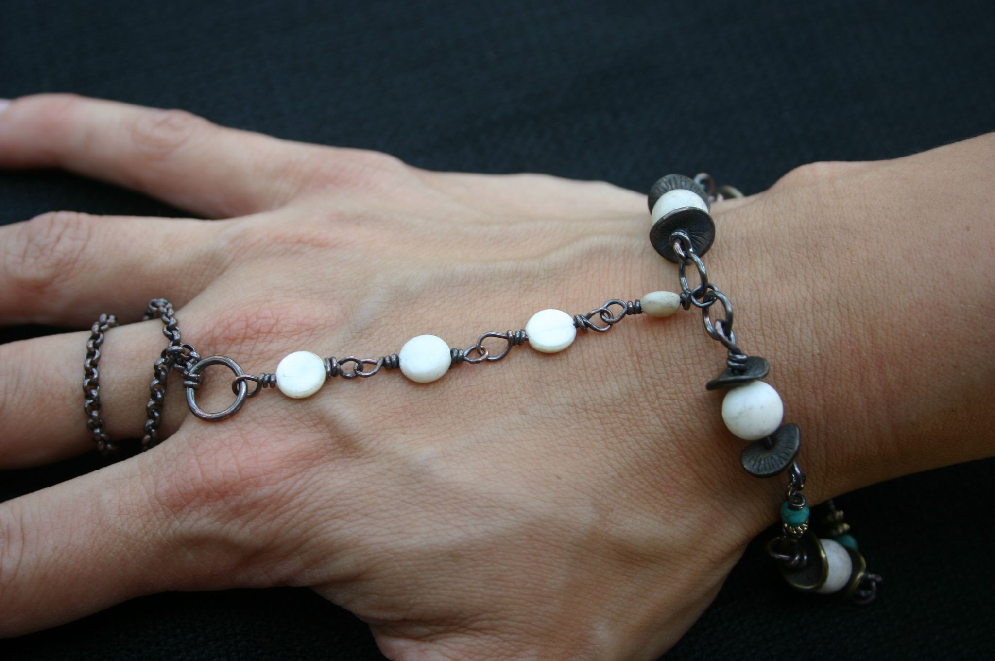 Mother of pearl beads enclosed with wavy discs and copper chain.