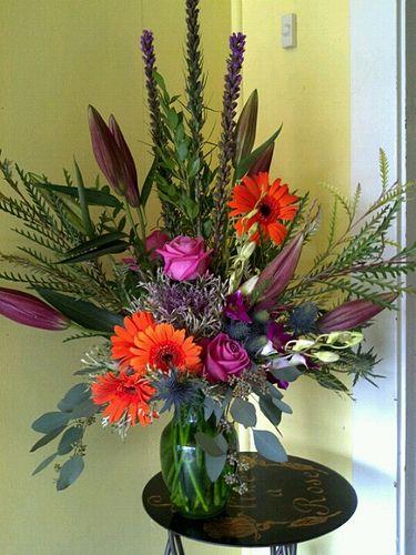 gerbera daisies, liatris, grevelia, dendrobium orchids, soul mate roses, sea holly, myrtle, seeded eucalyptus, flowering kale