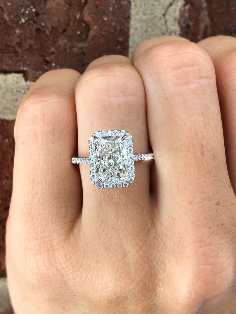 This gorgeous custom diamond engagement ring features a radiant cut diamond center adorned with a delicate diamond halo and thin diamond band. The perfect style ring for an elegant and brilliant look. Handcrafted by Ascot Diamonds.  #haloengagementrings #radiantcut #ascotdiamonds #engagementrings #halorings