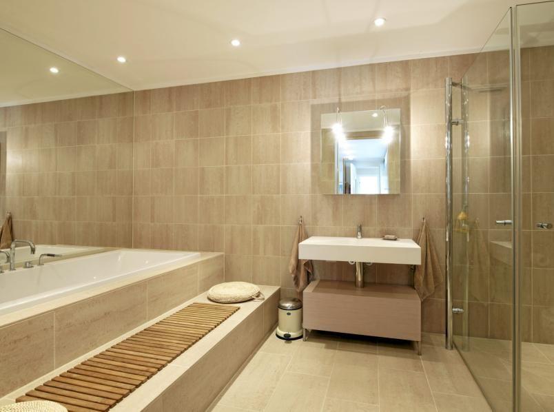 Badekaret er innebygd i de beige flisene, med en praktisk sittebenk foran. Hele veggen bak badekaret er dekket av en ren speilflate som forstørrer rommet.