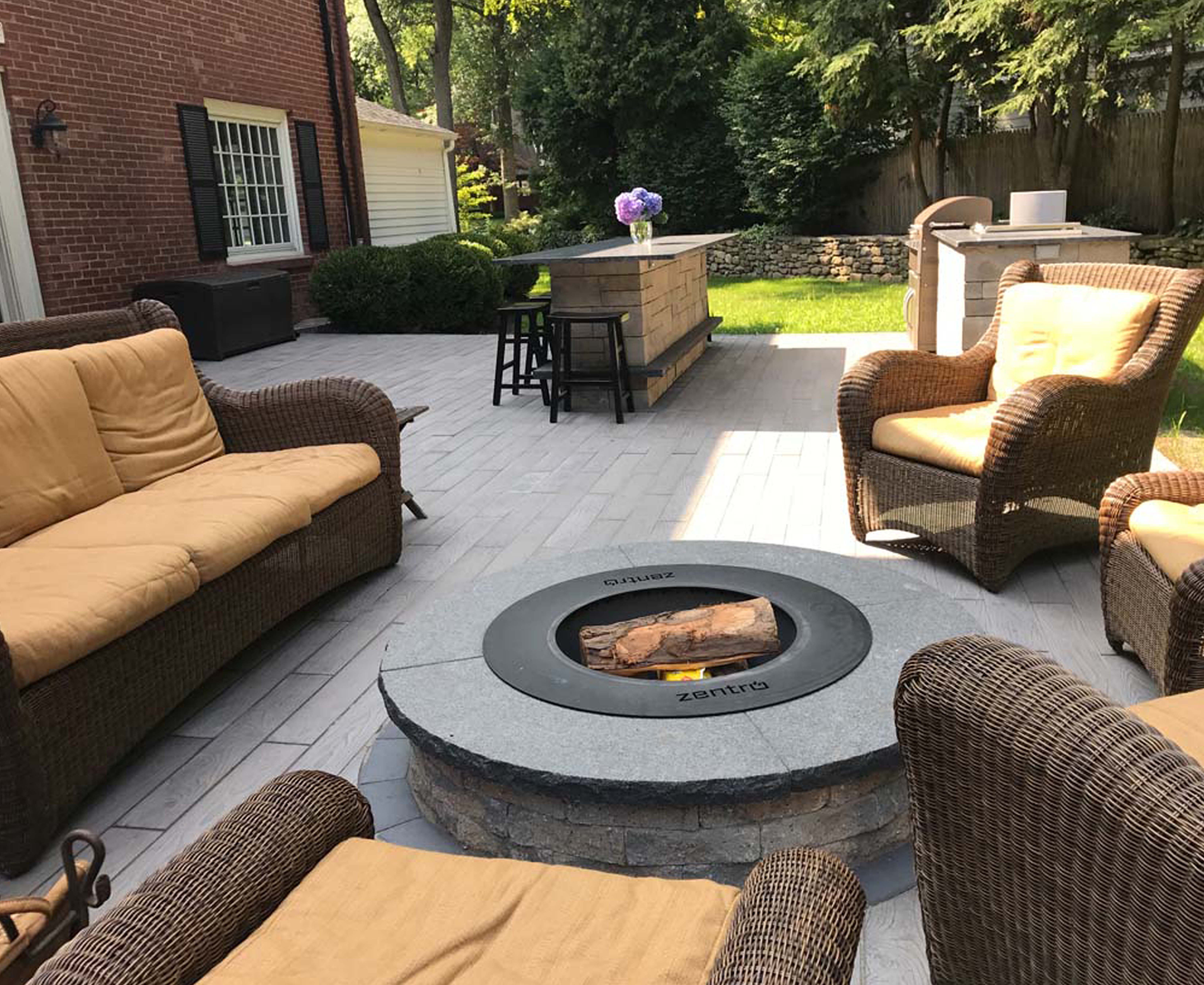 A smokeless fire pit and an outdoor kitchen with a bar built by