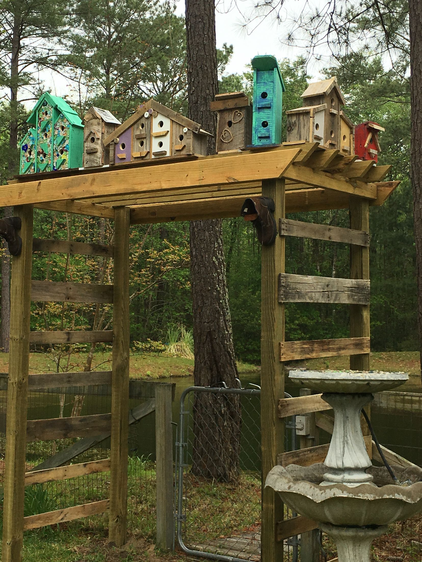 Birdhouse arbor made from scrap wood and pallet boards and scrap lumber to make the birdhouses. Looks over the catfish pond in our backyard