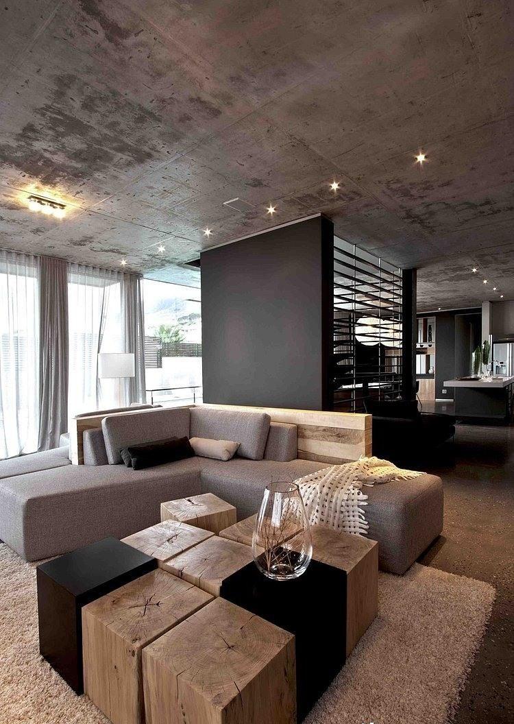 Wohnzimmer Grau  Eckcouch Baumstumpf Holzbloecke Couchtisch Betondecke Minimalistisch
