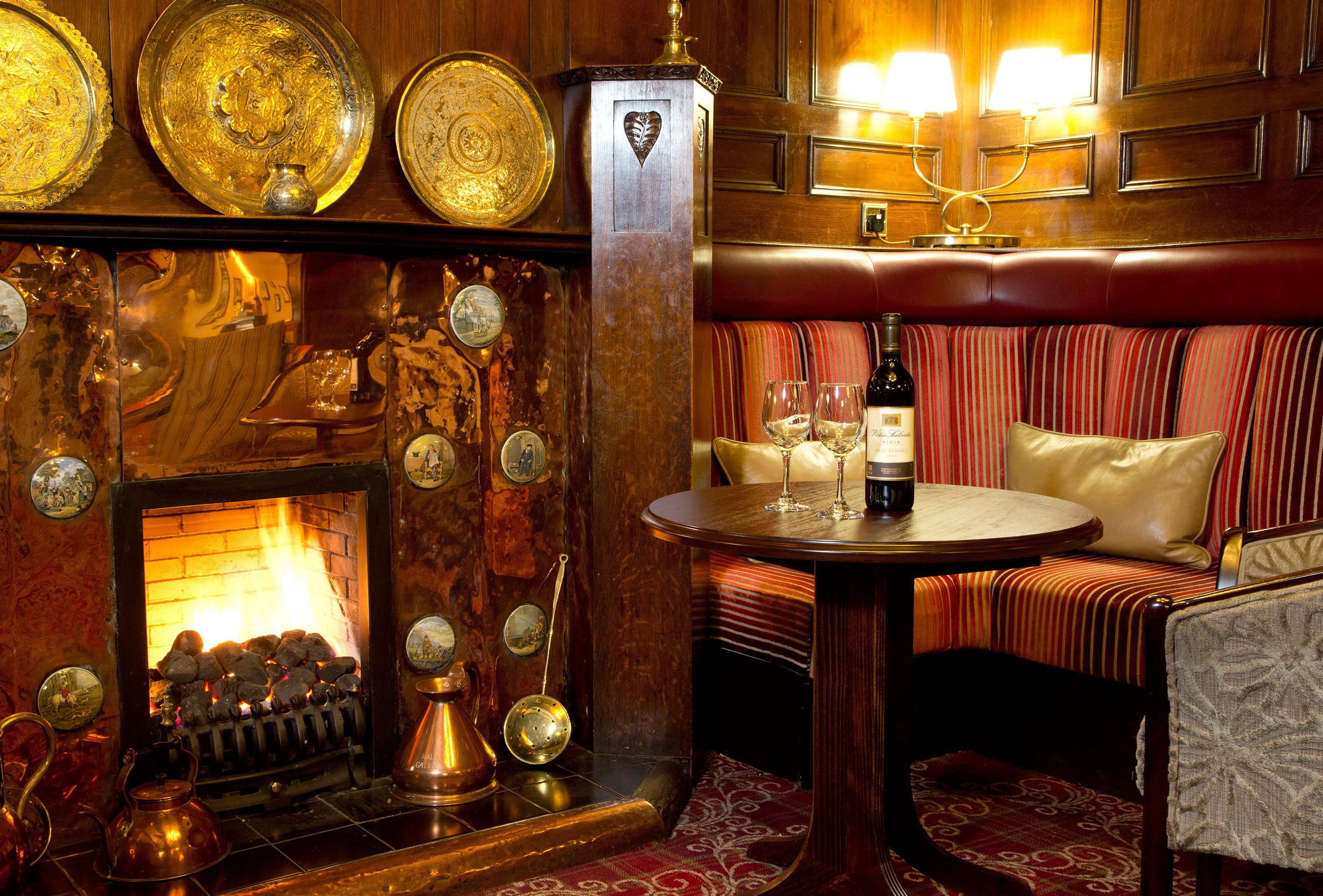 A glass of wine by the fire in the cosy surrounds of an Lakeland hotel | The George Hotel, Penrith