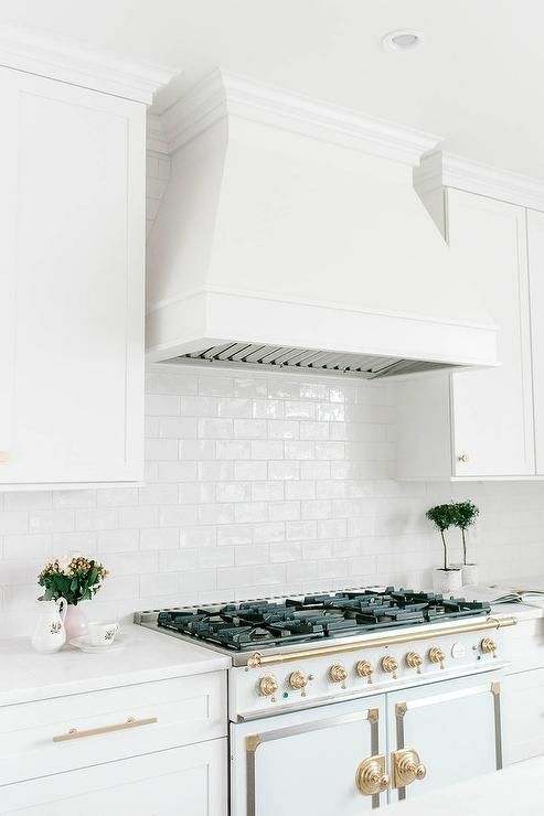 La Cornue CornuFe Range enveloped around white shaker cabinets, brass pulls and white quartz countertops. #whiteshakercabinets