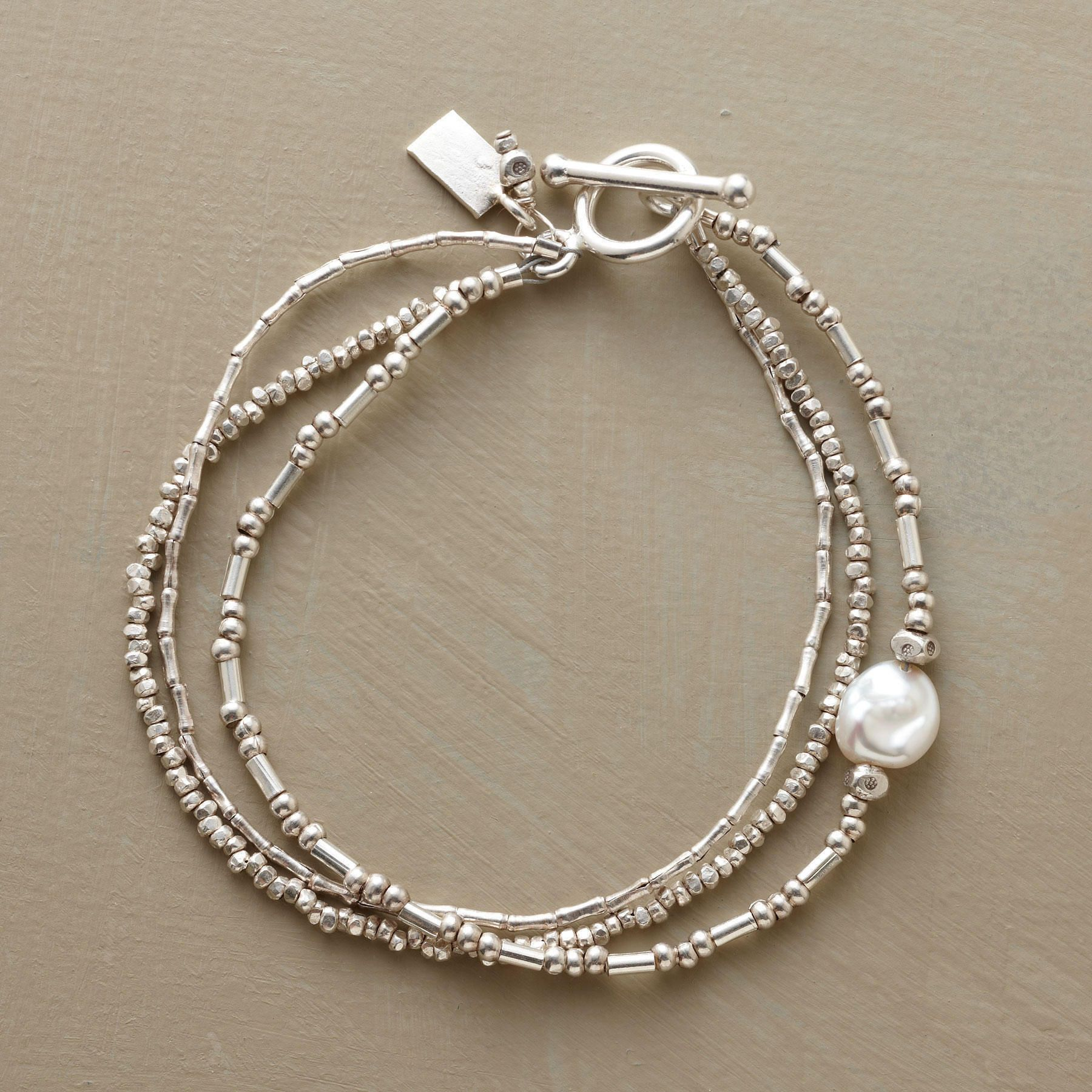"""PEARLS IN THE STREAM BRACELET--A luminous freshwater pearl punctuates a rippling rivulet of triple-strand sterling silver beads strung in three different beading arrangements. Made in USA. Exclusive. 7-1/2""""L."""
