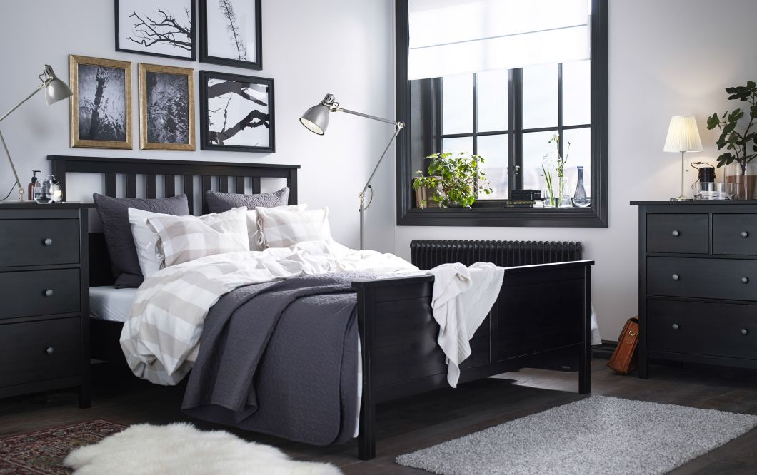 A large bedroom with a blackbrown bed with bed textiles