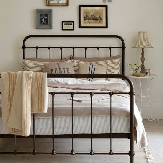 wrought iron bed with gallery wall and simple bedside table