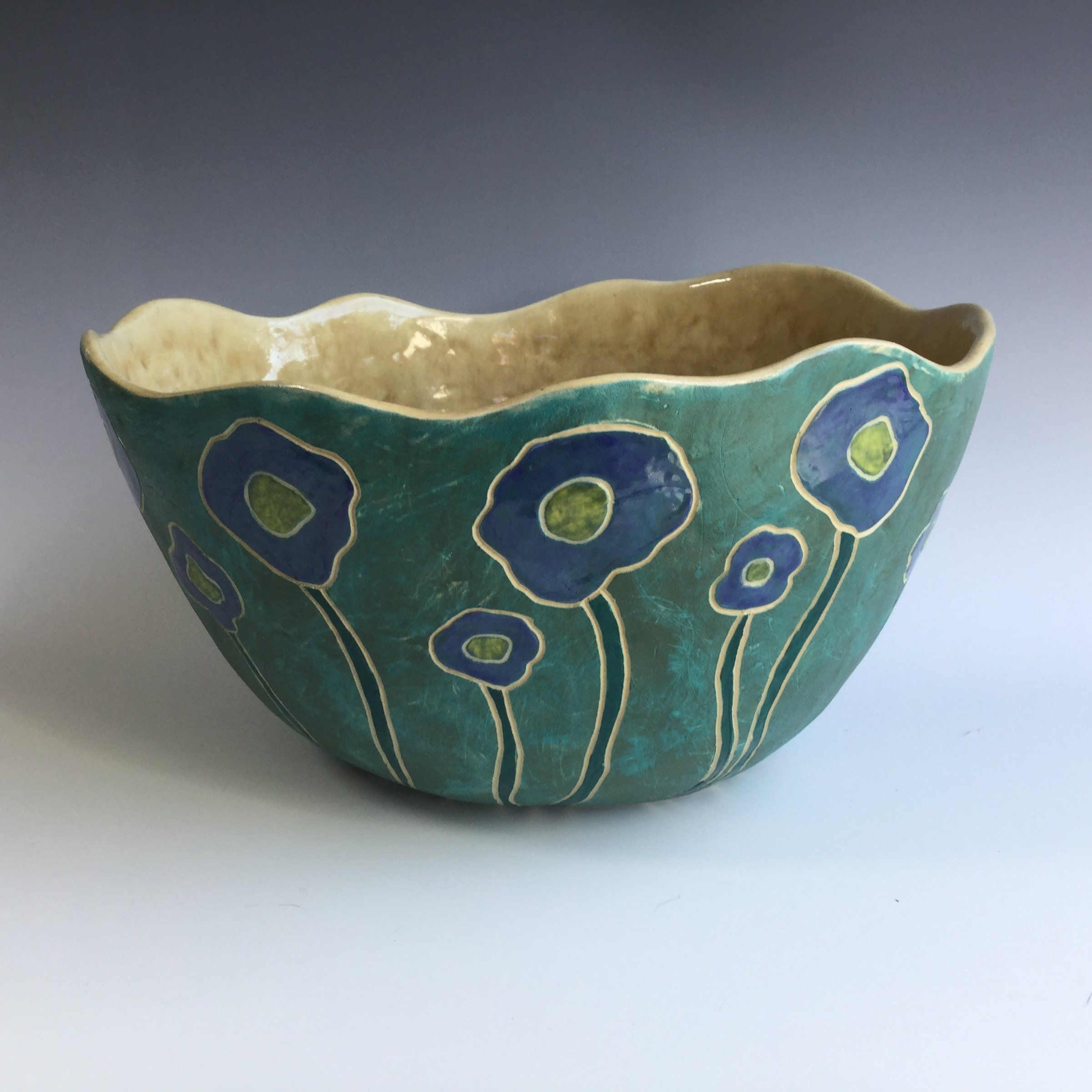 Ceramic Bowl - This Cornflower Bowl is a large hand-built stoneware bowl made by using pinching and coiling techniques. The outside was carefully carved, and colored underglazes were applied before the first firing. A glaze was applied before the second firing to add color contrast and functionality. The bowl can safely be washed by hand or in the dishwasher. It makes a wonderful statement piece or gift. Holds approx. 40 oz.