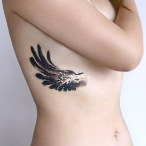 Acrylic style wing tattoo on the right side ribcage. Tattoo...