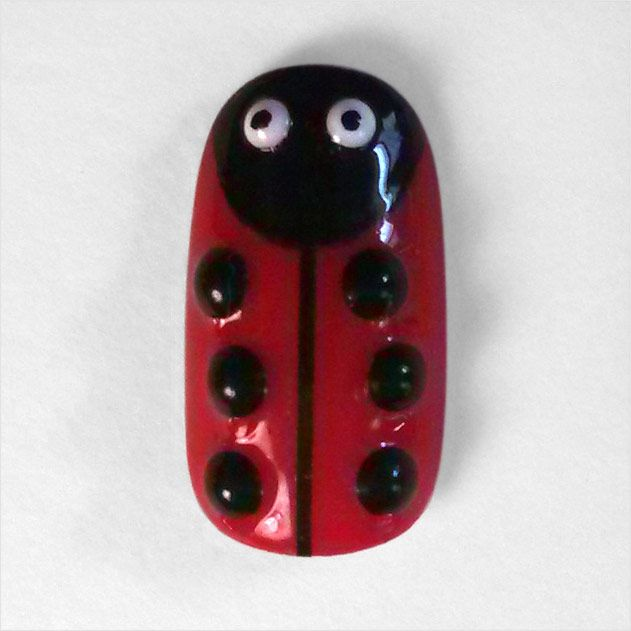 """What else is there to say but cute?! In tribute to Sesame Street's """"Ladybug Picnic,"""" I present to you, """"Ladybug."""" And she's no ordinary ladybug; this one is created with colored stones and striping tape instead of just polish… it's a little 3D bug for your fingertips!"""