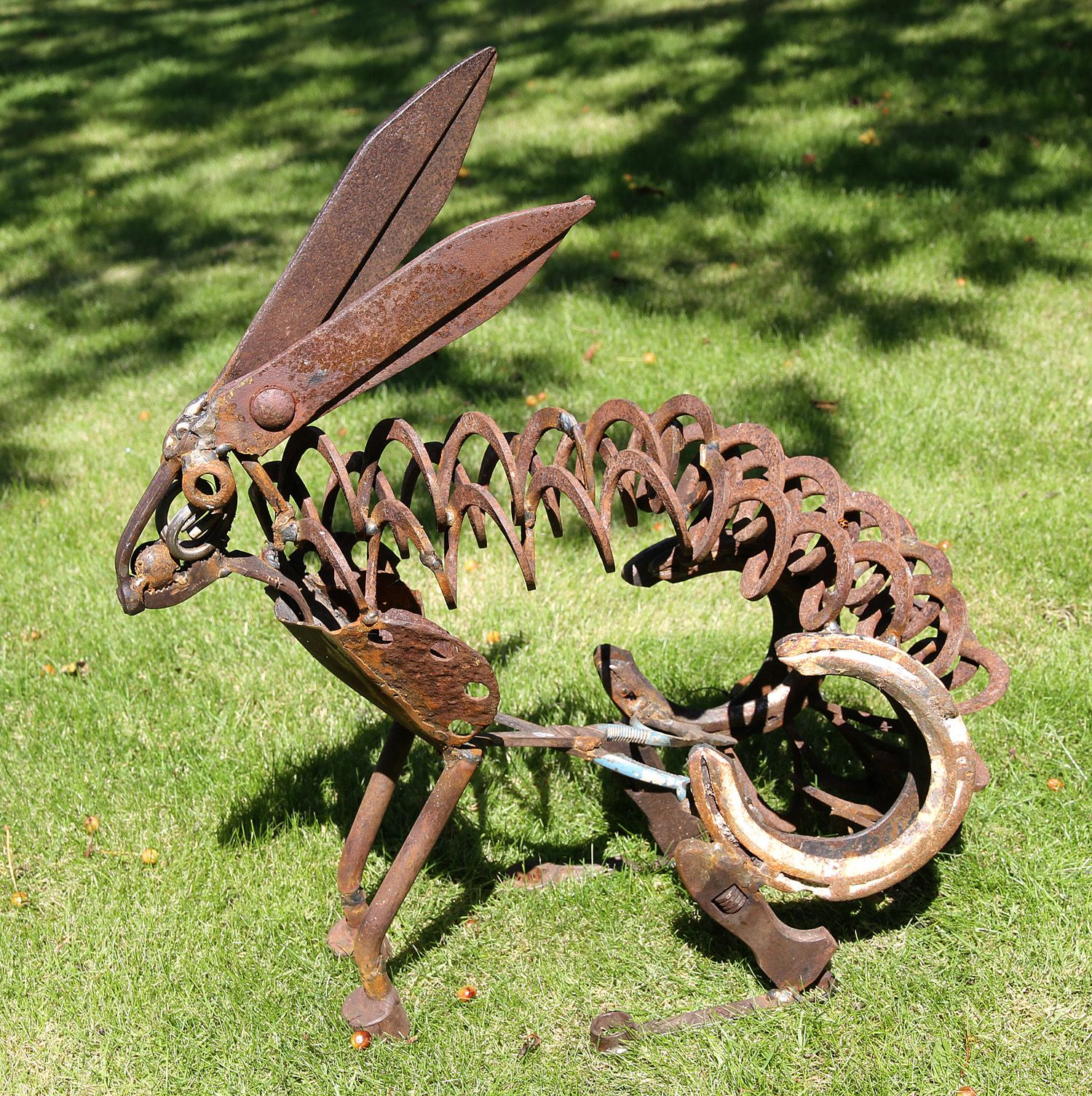 Metal yard sculptures hang on a minute rusty old garden for Lawn ornaments for sale