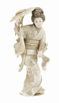 A Japanese ivory okimono of a dancing lady Meiji (1868-1912) Carved wearing a flowing kimono, holding a fan in one hand, and an attribute in her other hand over her head. 19 cm. high