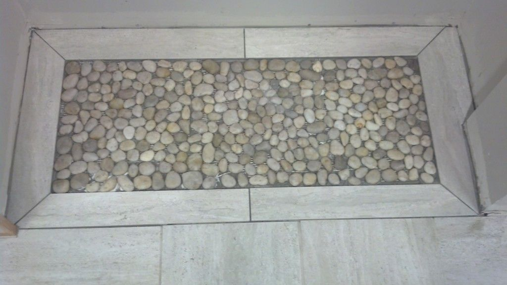Pebbles installed in a rug pattern.