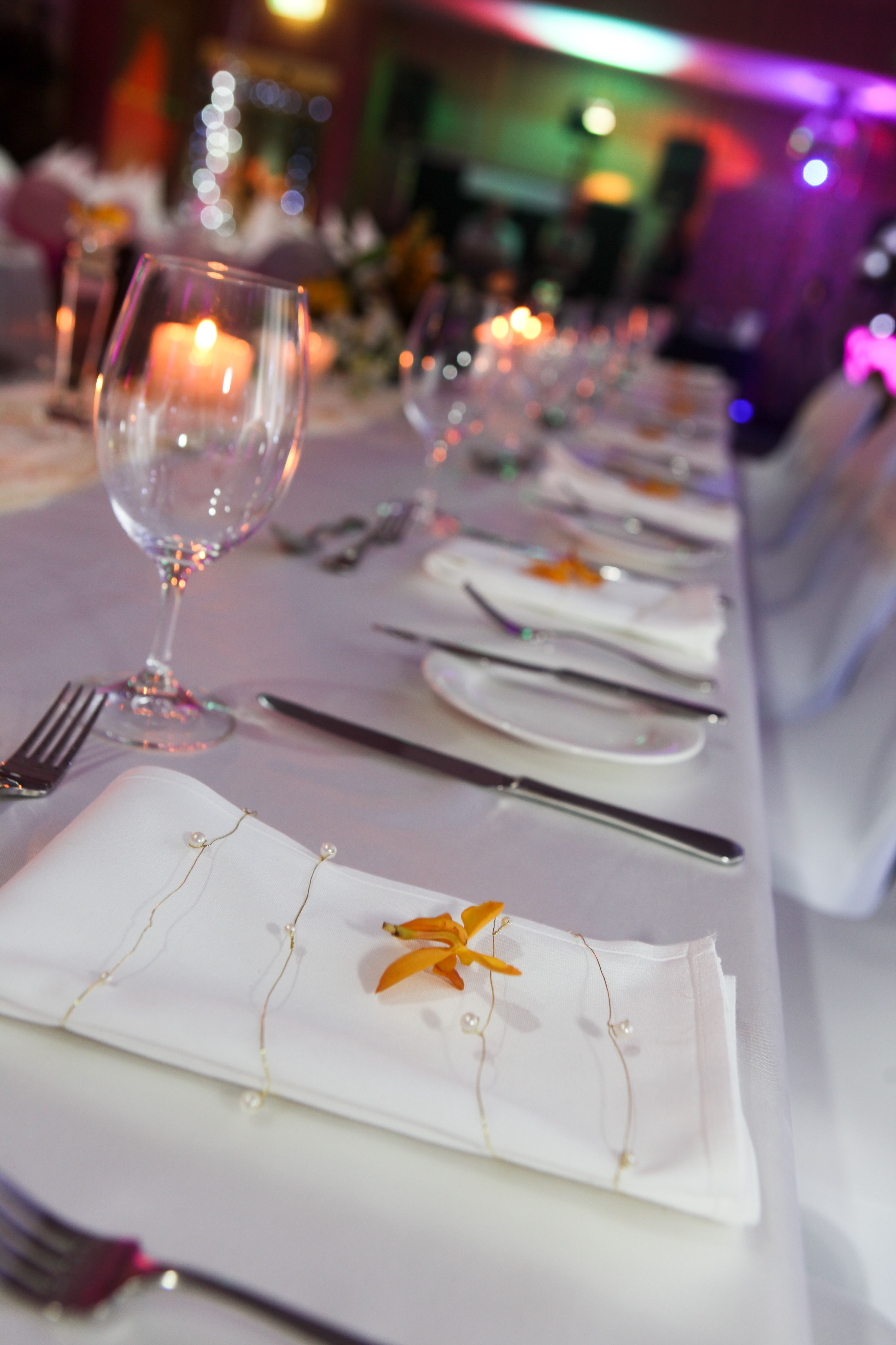 A simple way to add colour to the bridal & guest tables is by placing an orchid on each napkin