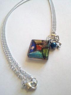 """Interesante collar hecho con cadena en color plata.  Pendant en cristal pintado simulando vitral.  Incluye tres mini llaves y una perloita color azul metalico.    Definitivamente un collar super original.  Mide aprox. 23""""."""