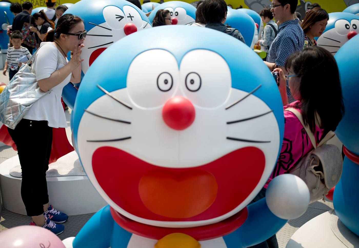 04/30/14. Visitors look at models of Doraemon, one of Japan's most popular animation characters, during the 100 Doraemon Secret Gadgets Expo held outside a shopping mall in Beijing, China, on Wednesday. The expo, which displays 100 life-sized Doraemon models with different gestures and facial expressions, runs until June 22. AP photo. Source; JapanToday