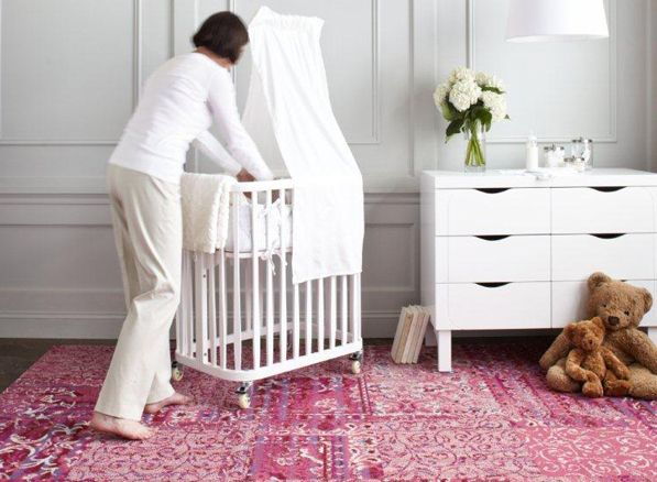 Light grey walls, clean white furniture and colourful floor rugs.
