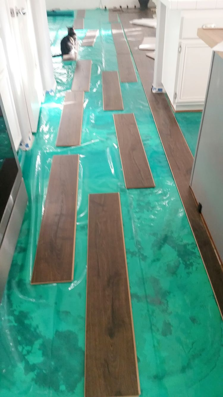 Pergo flooring laid out for installation between family room and kitchen