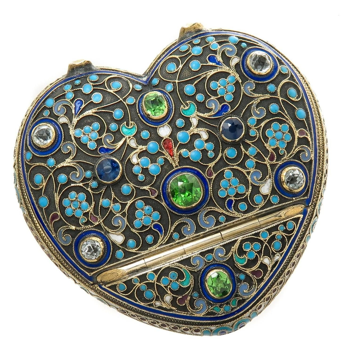 Russian Enamel and Gem set Heart shape box for Tiffany & Company | Circa 1890 Russian Silver and Cloisonee Enamel, Heat shape Trinket box for Tiffany & Company, Centrally set with a very fine Cushion cut Green Demantoid Garnet measuring at 1 Carat and two additional Cushion cut Demantoid Garnets measuring at 1/2 carat each, further set with Blue and White Sapphires.