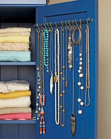 Great idea for storing necklaces & bracelets...a thin wooden dowel mounted inside a closet or cabinet door using cup hooks is the foundation of a simply chic jewelry hanger.