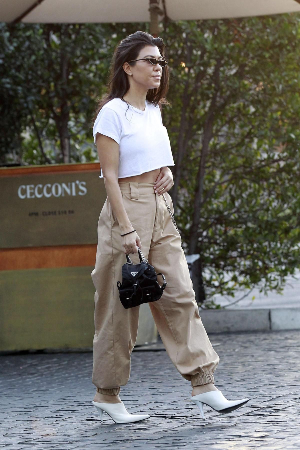 1ef269dae742 Kourtney Kardashian wearing Prada Vela Backpack, Celine White Pointed  Mules, I.am.gia Cobain Pants and Re/done 1950s Boxy Tee