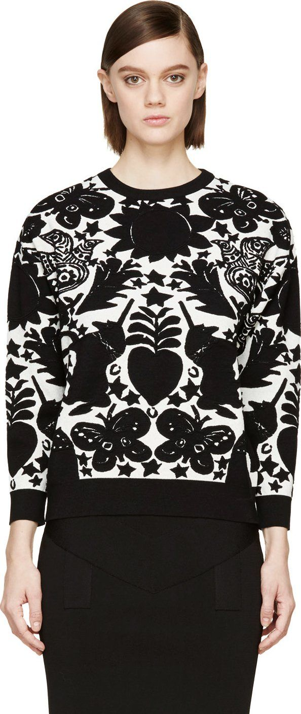 Long sleeve pullover sweater in black and vanilla white jacquard motif featuring silhouettes of butterflies, unicorns, hearts, stars, sunflowers and peace doves. Ribbed crewneck collar, sleeve cuffs, and hem. Tonal stitching.