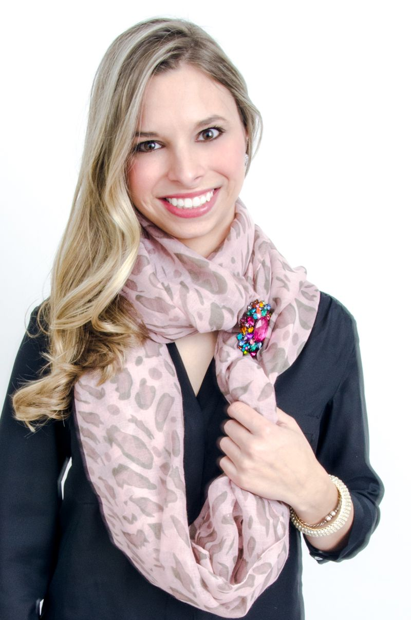 Ashley uses a colorful jeweled brooch to her faded leopard print infinity scarf.