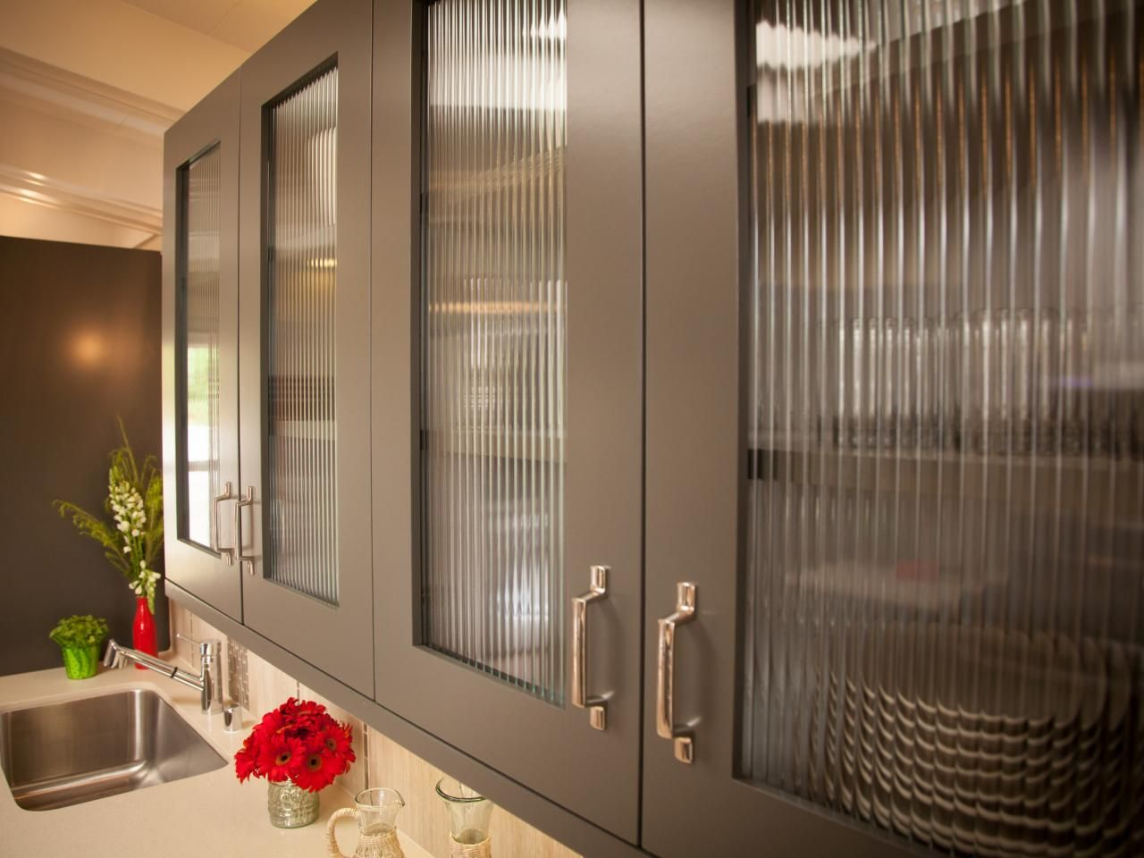 The glass doors on these gray kitchen cabinets lend a modern feel ...