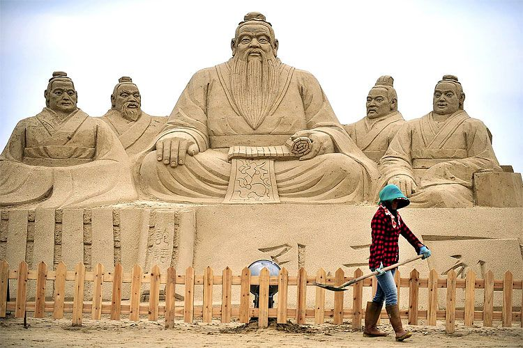 A woman shovels sand in front of sculptures of Confucius, center, a famed thinker and philosopher in Chinese history, and his disciples, at a beach culture festival in Pingtan county.