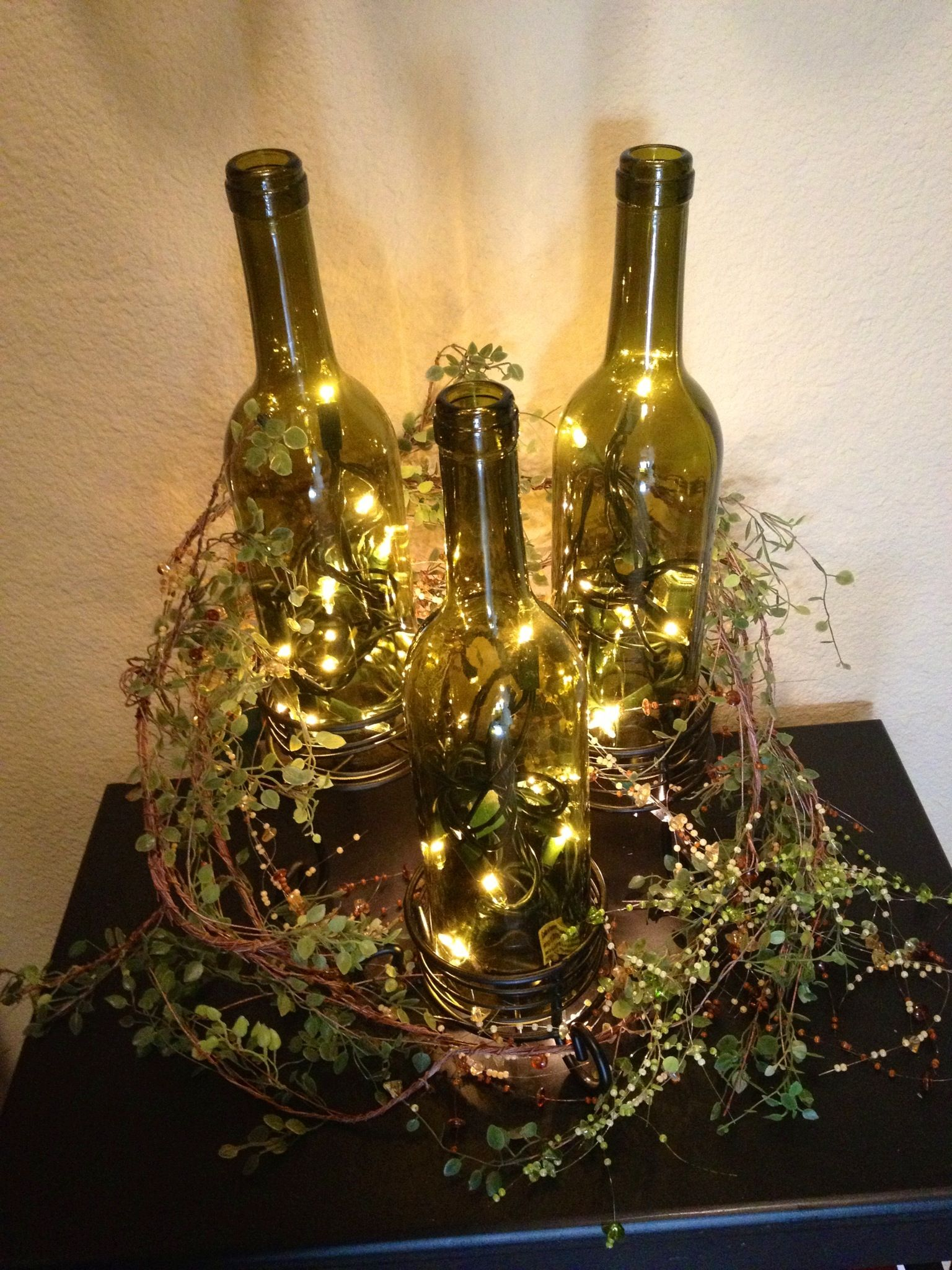 3 wine bottles placed on candle holders of different sizes for Christmas bottle decorations