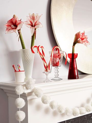 Candy canes, vases of red-and-white amaryllis, and a garland of fluffy pom-poms across the mantel create a sweet scene for Christmas. Editor's Tip: To enhance the look, add greenery and plump red pomegranates to the lineup.