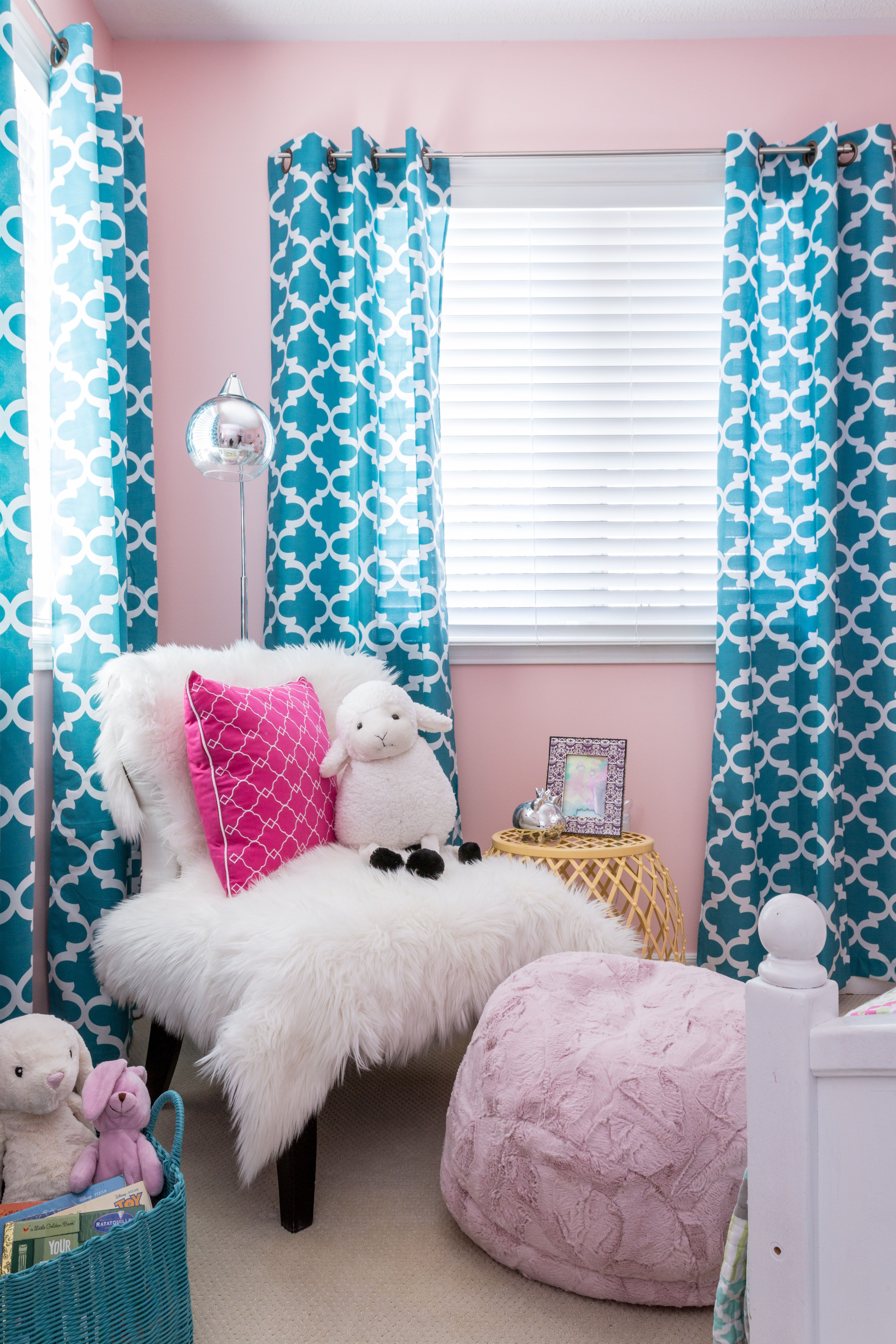 Little girls reading area pink walls blue patterned curtains sheep skin chair pink puff
