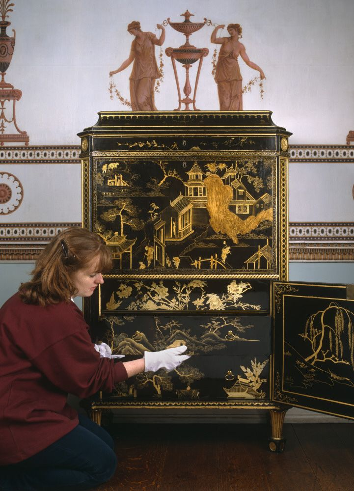 conservator handling one of the drawers of the chippendale attributed secretaire veneered with chinese lacquer at osterley park west london