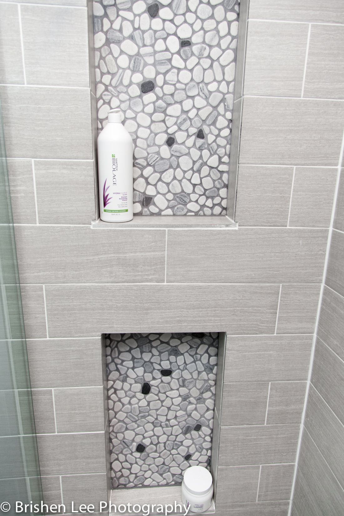 Two shower nooks with marble pebbles and horizontal grey porcelain ...