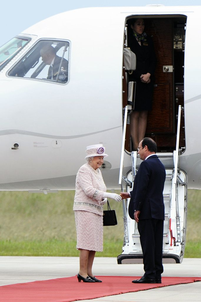 Queen Elizabeth II and French President Francois Hollande review French troops during a departure ceremony at the Villacoublay airport on June 7, 2014