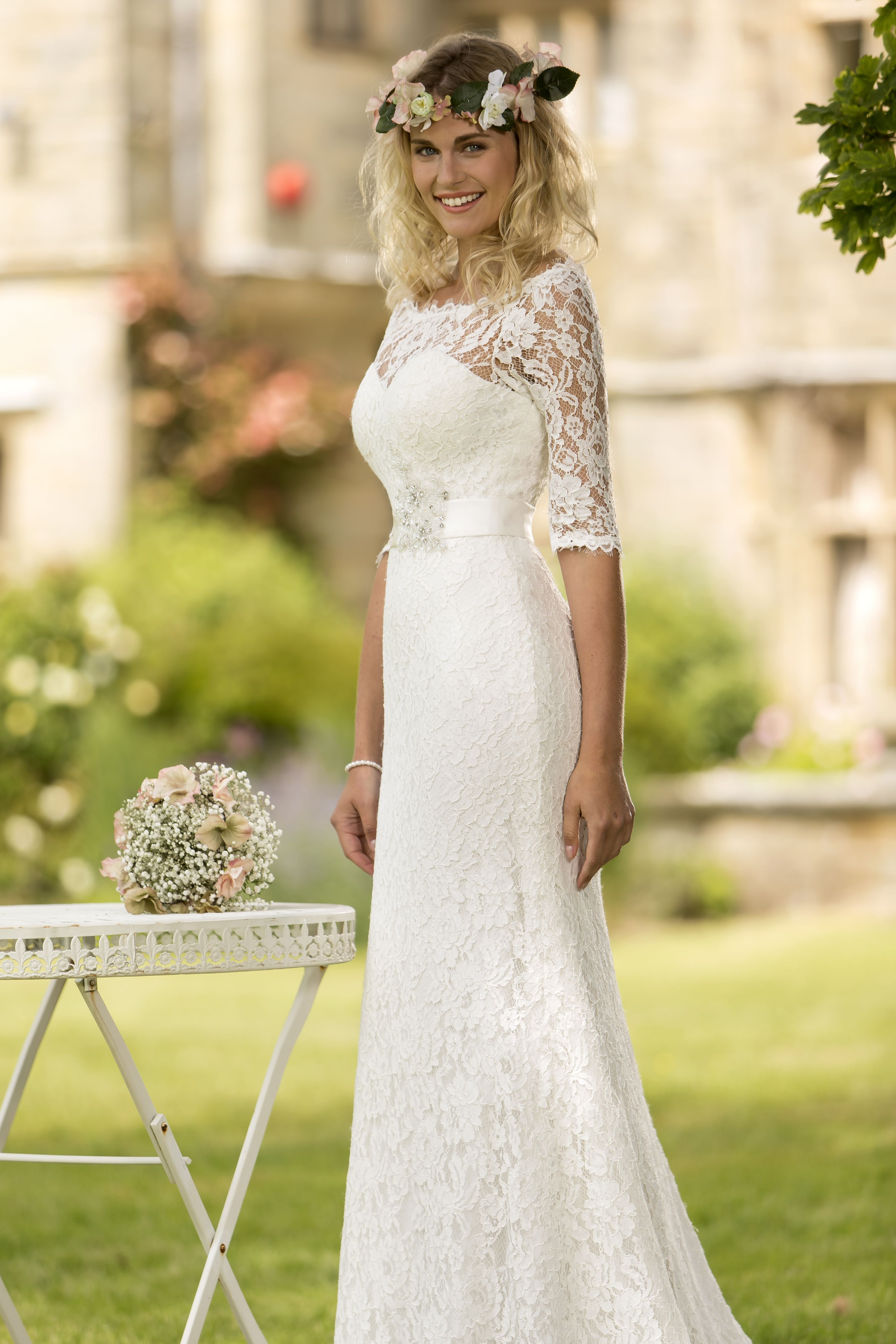 W186 -  Stunning corded lace bridal gown with bateau neckline and sleeve trimmed with a delicate lace scallop edge. Satin sash to waist embellished with a silver beaded applique. This gown is lined with the softess jersey which gives drape and movement to this elegant design. Zip up back with buttons and elasticated loops for a neat finish