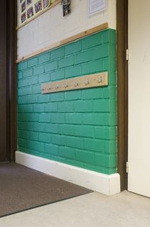 Film MACtac OLFactive appliqué sur les murs en brique d'une école maternelle.  « Depuis que la solution OLFactive™ a été installée, les odeurs de couches et d'urine ne sont plus gênantes. Par ailleurs, le revêtement mural OLFactive™ reste propre plus longtemps qu'un mur peint et résiste mieux aux rayures et aux taches que la peinture. »
