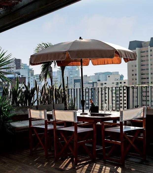 Terraço social | Para as refeições ao ar livre, mesa da L'Oeil, cadeiras da extinta Tribu e bancos feitos com madeiras reaproveitadas da obra (Foto: Evelyn Müller/Divulgação)